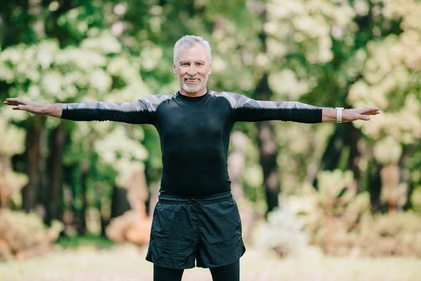 cheerful, mature sportsman smiling at camera while training in park - Photo, Image