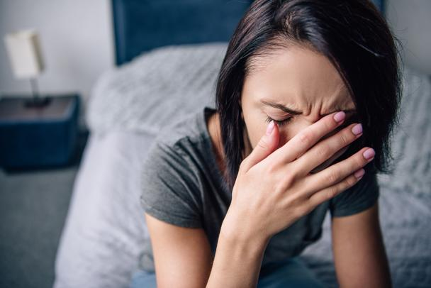 depressed woman sitting on bed at home, crying and covering face with hands - Photo, Image