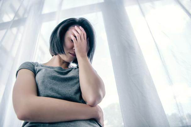 low angle view of depressed woman covering face at home - Photo, Image