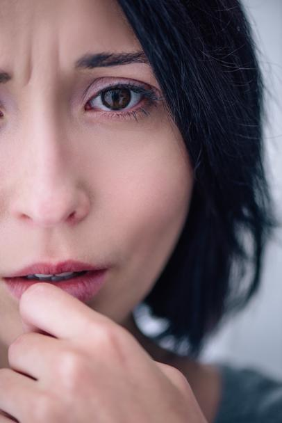 portrait of depressed brunette woman looking at camera at home - Photo, Image