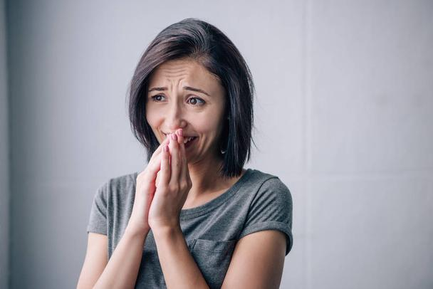 sad brunette woman covering mouth and crying at home - Photo, Image