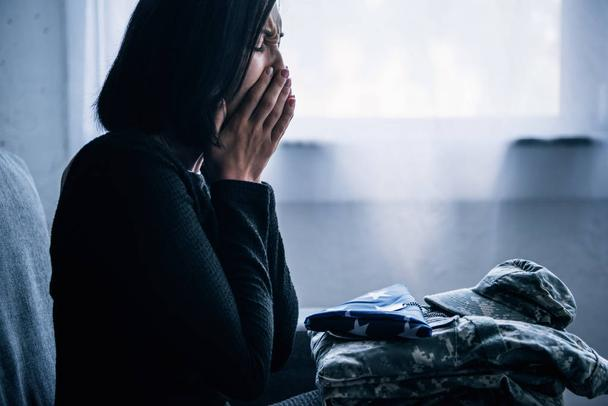 woman with military clothing and foded american flag crying at home - Photo, Image