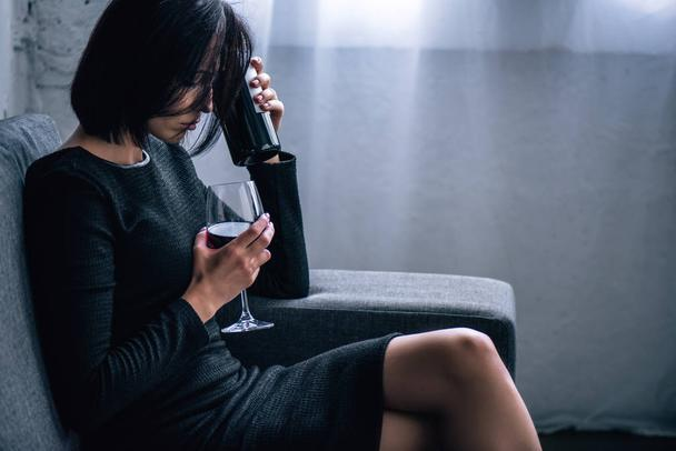 depressed woman sitting on sofa with wine glass at home - Photo, Image