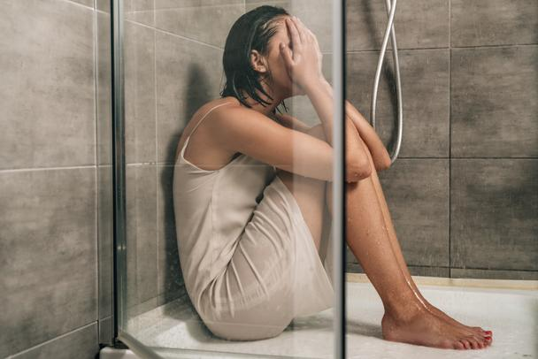 sad depressed woman covering face while sitting in shower at home - Photo, Image