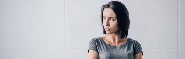 panoramic shot of depressed brunette woman looking away at home - Photo, Image