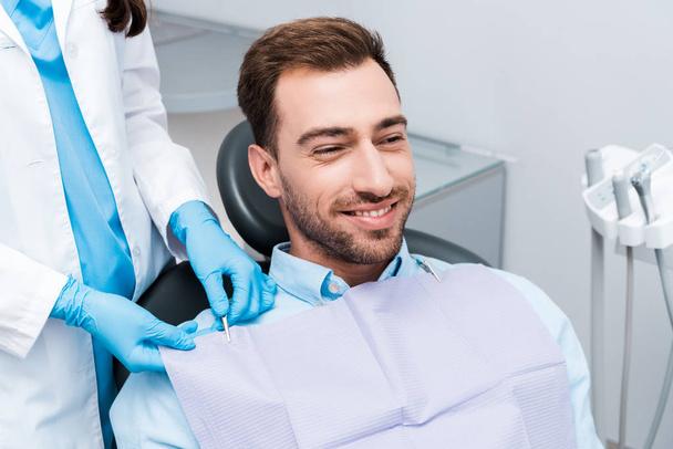 neşeli hastanın yanında duran mavi lateks eldiven diş hekimi kırpılmış görünümü  - Fotoğraf, Görsel