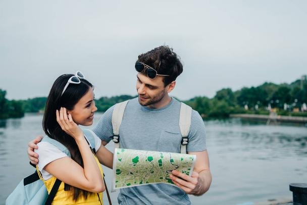 handsome man holding map and looking at asian woman - Photo, Image