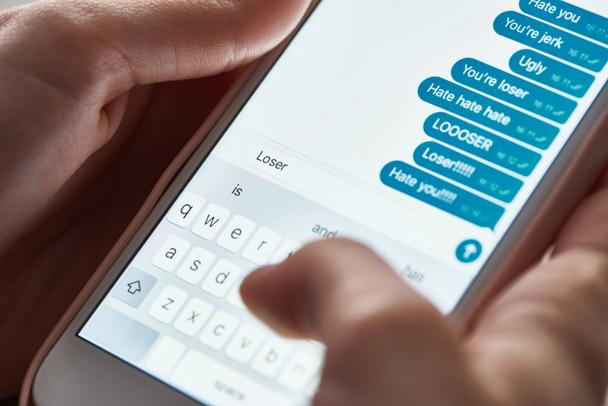 partial view of abuser sending offensive messages while using smartphone, illustrative editorial - Photo, Image