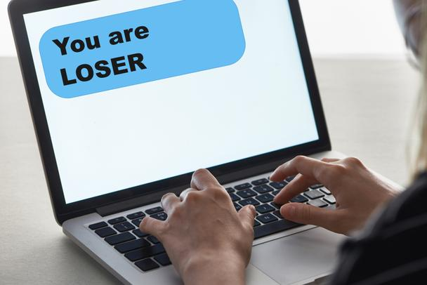 cropped view of girl typing on laptop keyboard with you are loser message on screen, cyberbullying concept - Photo, Image