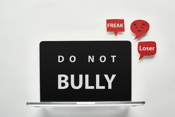 laptop with do not bully lettering on screen on white background near red speech bubbles with offensive words, cyberbullying concept - Photo, Image