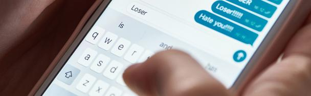 panoramic shot of abuser typing offensive messages while using smartphone, illustrative editorial - Photo, Image