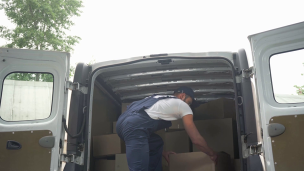 delivery man taking cardboard boxes from car  - Footage, Video