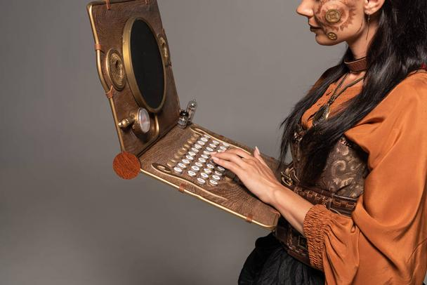 cropped view of woman using steampunk laptop isolated on grey - Photo, Image