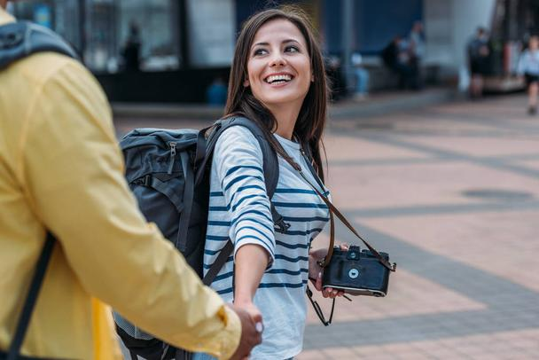 Woman with digital camera and backpack holding hand of friend  - Photo, Image