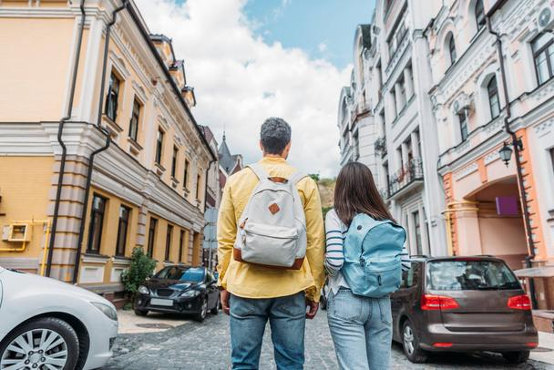 back view of mixed race man and girl standing on street near buildings - Photo, Image