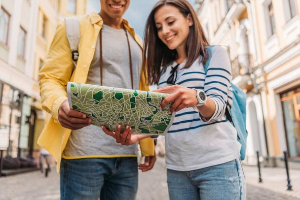 cropped view of cheerful mixed race man holding map near happy girl  - Photo, Image