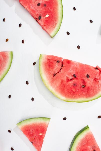 вид сверху на вкусные ломтики арбуза с семенами на белом фоне  - Фото, изображение