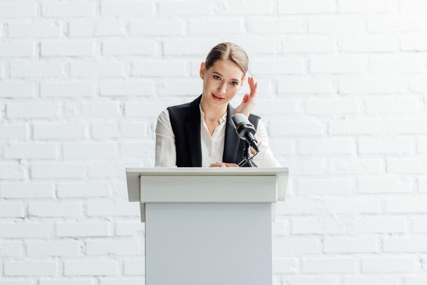 attractive businesswoman standing and talking during conference in conference hall - Photo, Image