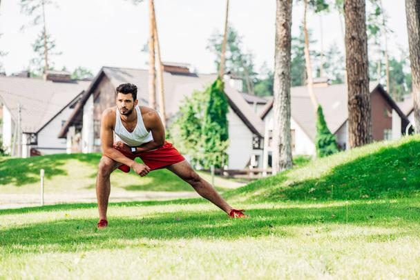 handsome man warming up while exercising on lawn  - Photo, Image