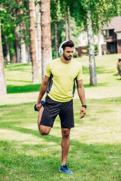 handsome man exercising while listening music in headphones  - Photo, Image