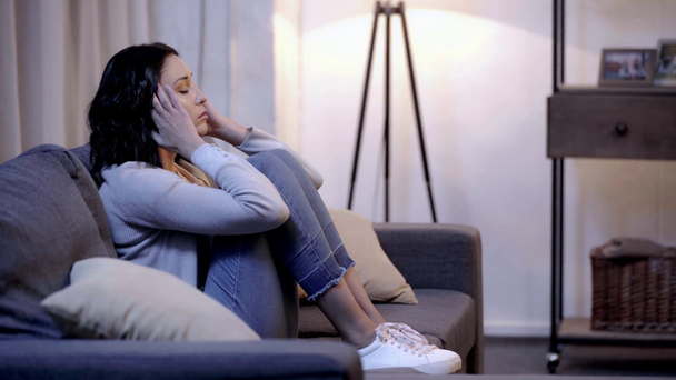side view of sad woman sitting on sofa  - Footage, Video