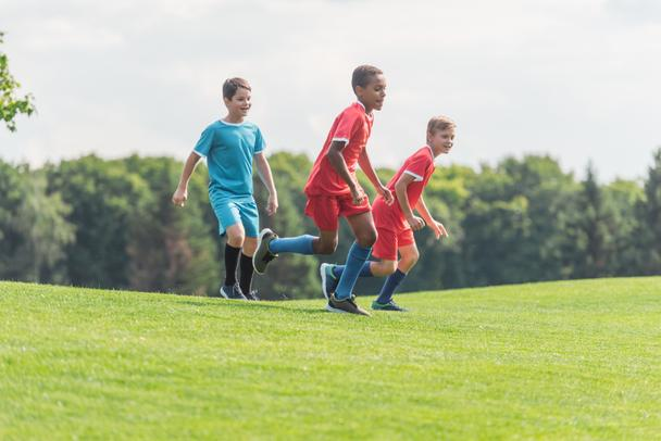 happy multicultural boys running on grass  - Photo, Image