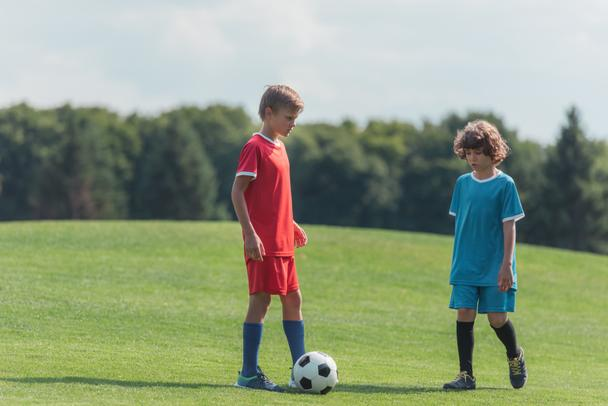 cute curly boy playing football with friend on grass in park  - Photo, Image