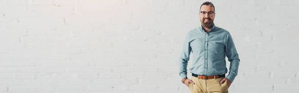 panoramic shot of handsome and smiling businessman in shirt with hands in pockets  - Photo, Image