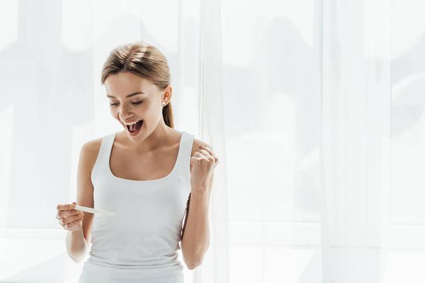 smiling young woman holding pregnancy test and showing yes gesture at home - Photo, Image