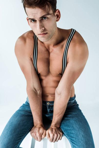 sexy man in suspenders sitting on chair and looking at camera on white  - Photo, Image