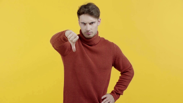 upset man in sweater showing thumb down isolated on yellow - Footage, Video