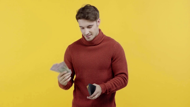 successful man in sweater showing money isolated on yellow - Footage, Video