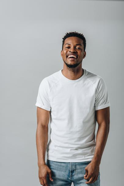 African American man in white T-short laughing and looking at camera isolated on grey - Photo, Image