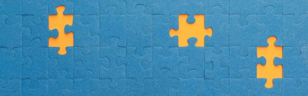 panoramic shot of blue jigsaw puzzle with yellow gaps - Photo, Image