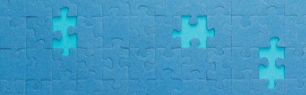 panoramic shot of blue jigsaw puzzle with lighter gaps - Photo, Image