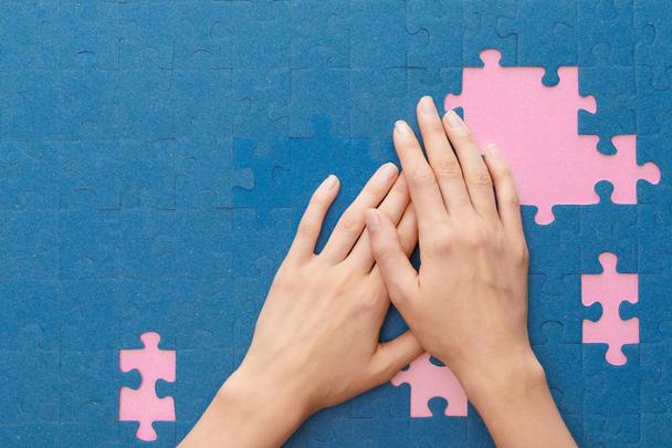 cropped view of woman covering blue jigsaw puzzle on pink background - Photo, Image