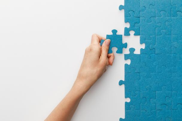 cropped view of woman attaching blue jigsaw puzzle on white background - Photo, Image