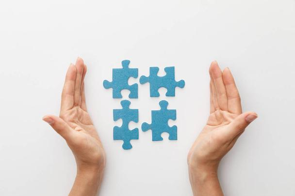 cropped view of woman hands near pieces of blue jigsaw puzzle on white background - Photo, Image