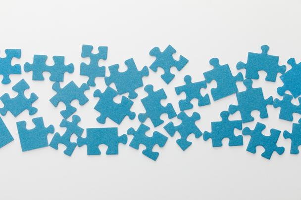 top view of scattered pieces of blue jigsaw puzzle on white background - Photo, Image