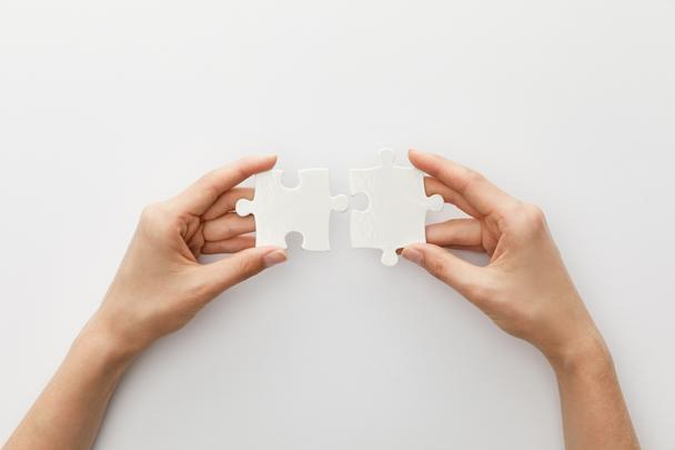 cropped view of woman holding piece of jigsaw puzzle on white background - Photo, Image