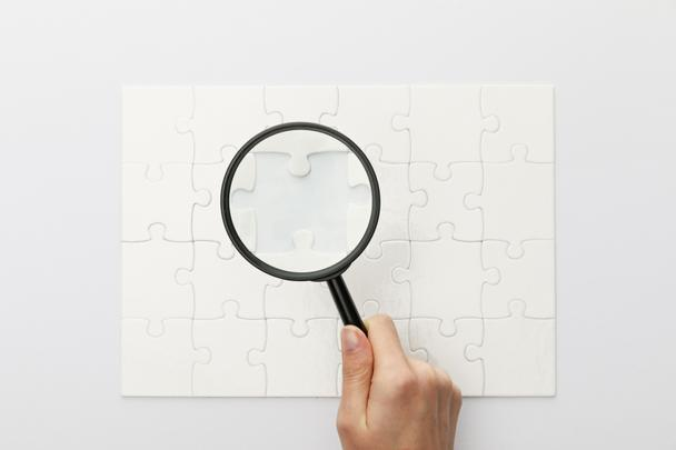 cropped view of woman holding magnifying glass under jigsaw puzzle on white background - Photo, Image