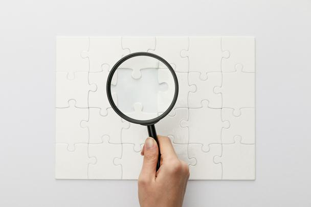cropped view of woman holding magnifying glass under jigsaw puzzle with lost piece on white background - Photo, Image