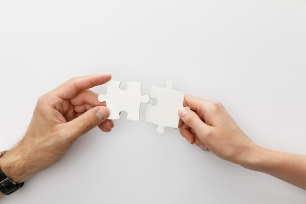 cropped view of woman and man holding pieces of jigsaw puzzle on white background - Photo, Image
