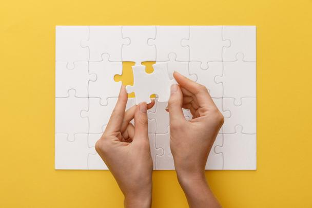 cropped view of woman holding piece of white jigsaw puzzle on yellow background - Photo, Image
