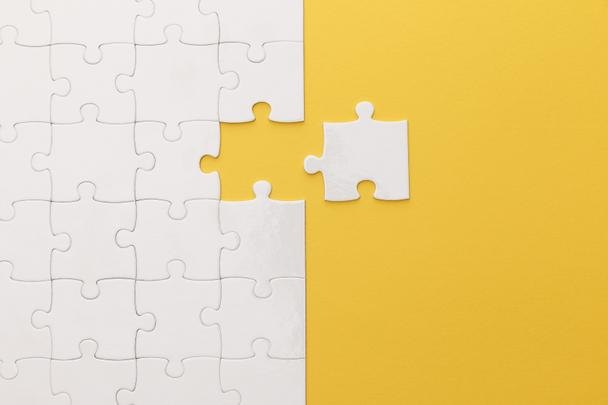 top view of white jigsaw puzzle on yellow background - Photo, Image