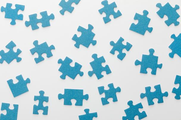 top view of scattered blue jigsaw puzzle on white background - Photo, Image