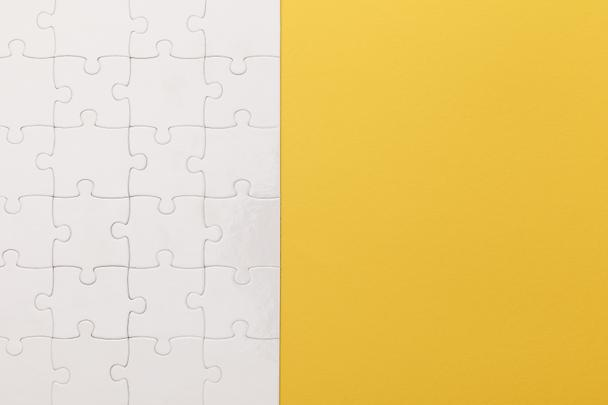 top view of white completed puzzle on yellow background - Photo, Image