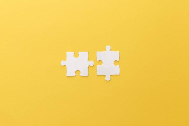 top view of white puzzle pieces on yellow background - Photo, Image