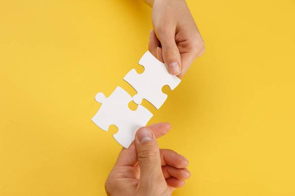 cropped view of woman and man matching pieces of white puzzle on yellow background - Photo, Image