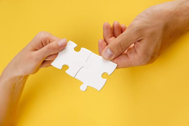cropped view of man and woman matching pieces of white puzzle on yellow background - Photo, Image